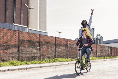 Young man riding bicycle with his girlfriend standing on rack - UUF10543