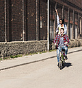 Young man riding bicycle with his girlfriend standing on rack - UUF10546