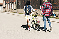 Young couple with bicycle and skateboard walking in the street - UUF10552