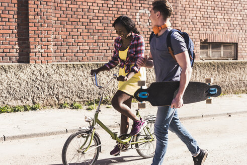 Young couple with bicycle and skateboard walking in the street - UUF10558
