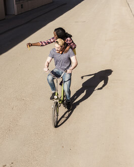 Young man riding bicycle with his girlfriend standing on rack, taking selfies - UUF10561