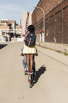 Young couple riding bicycle with girl standing on rack - UUF10564