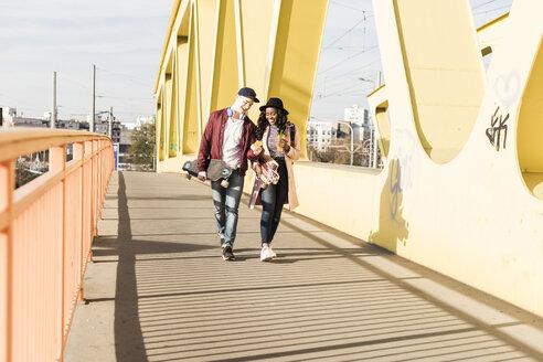 Young couple with skateboard walking on bridge - UUF10576
