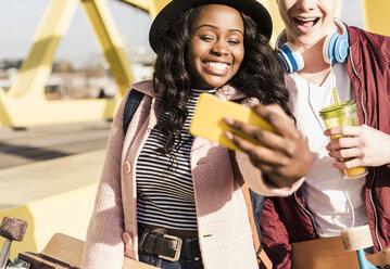Young couple walking on bridge, using smartphone - UUF10579