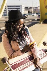 Young woman sitting on  bridge using smartphone - UUF10582