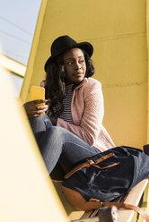 Young woman sitting on  bridge using smartphone - UUF10585