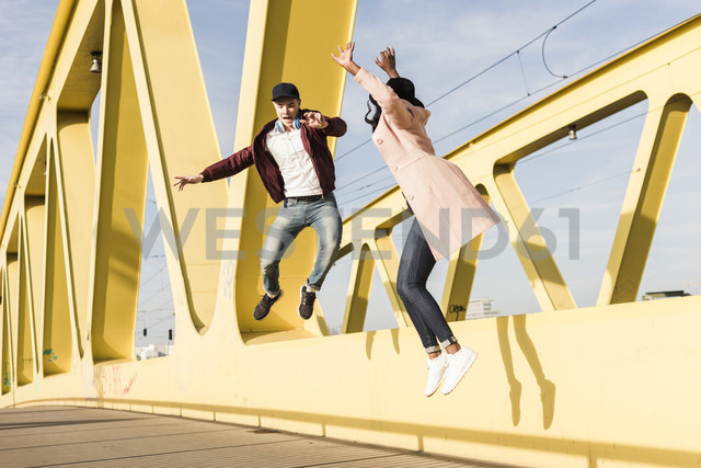 Happy couple jumping on bridge - UUF10588 - Uwe Umstätter/Westend61