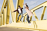 Happy couple jumping on bridge - UUF10588