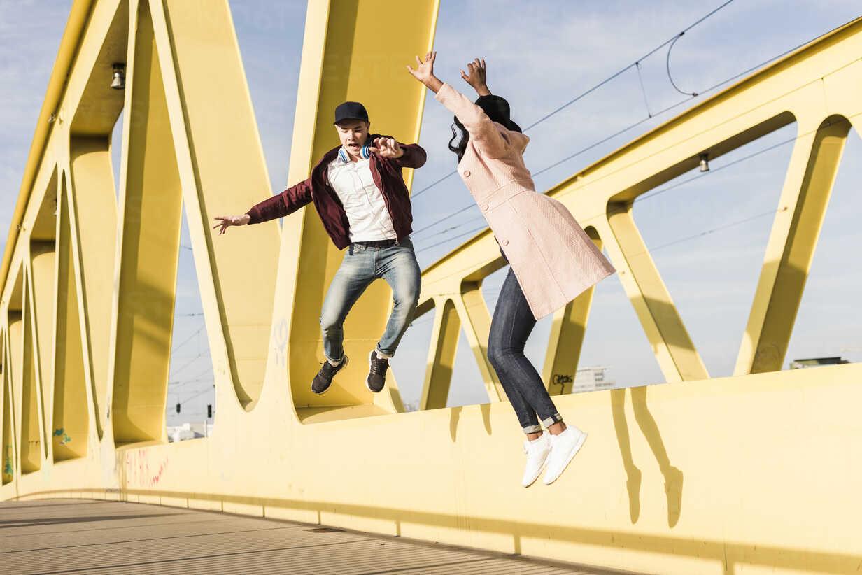 Happy couple jumping on bridge - UUF10588 - Uwe Umstätter/Westend61