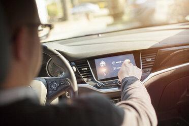 Man in car adjusting devices at home via smartphone - NAF00087