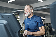 Fit senior man on treadmill working out in gym - HAPF01642