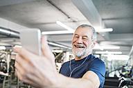 Happy senior man with smartphone and earphones in gym - HAPF01651