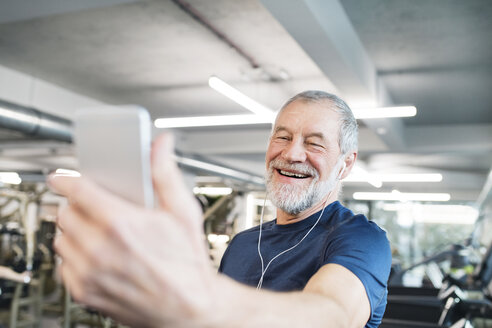 Happy senior man with smartphone and earphones in gym - HAPF01651