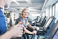 Group of fit seniors on treadmills working out in gym, woman smiling - HAPF01654