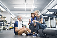 Group of fit seniors in gym resting after working out - HAPF01660