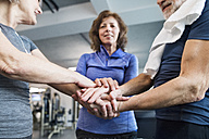 Group of fit seniors stacking hands in gym - HAPF01663