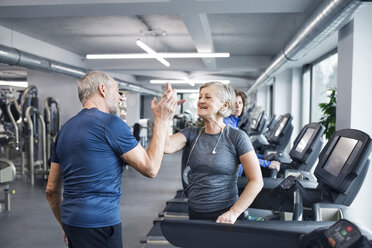 Happy senior man and woman high fiving after working out in gym - HAPF01666