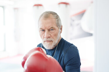Portrait of serious senior man with earphones and boxing gloves in gym - HAPF01672