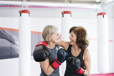 Two happy senior women with boxing gloves embracing in gym - HAPF01678
