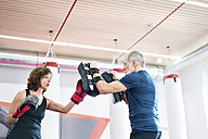 Fit senior woman boxing with her coach - HAPF01681