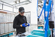 Man working in factory shop floor looking at product - DIGF02366