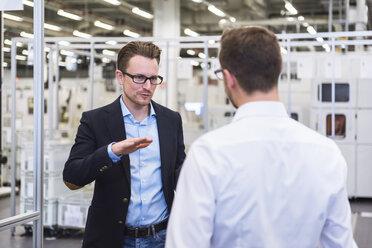 Two men talking in factory shop floor - DIGF02375