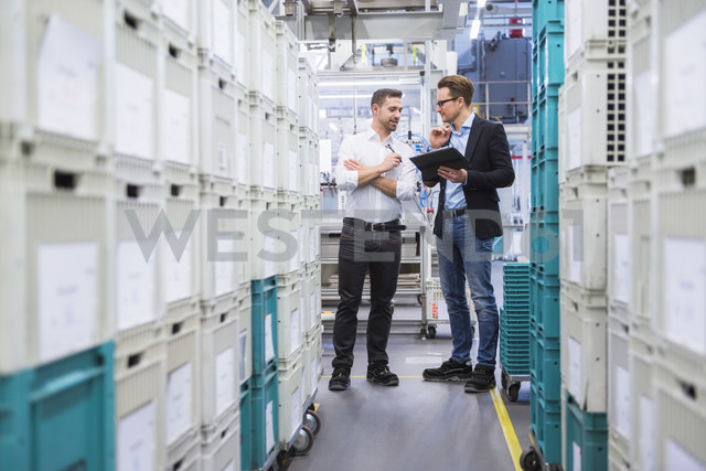 Two men with tablet talking at boxes in factory shop floor - DIGF02378 - Daniel Ingold/Westend61