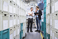 Two men with tablet talking at boxes in factory shop floor - DIGF02378
