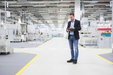 Man standing in factory shop floor taking notes - DIGF02384