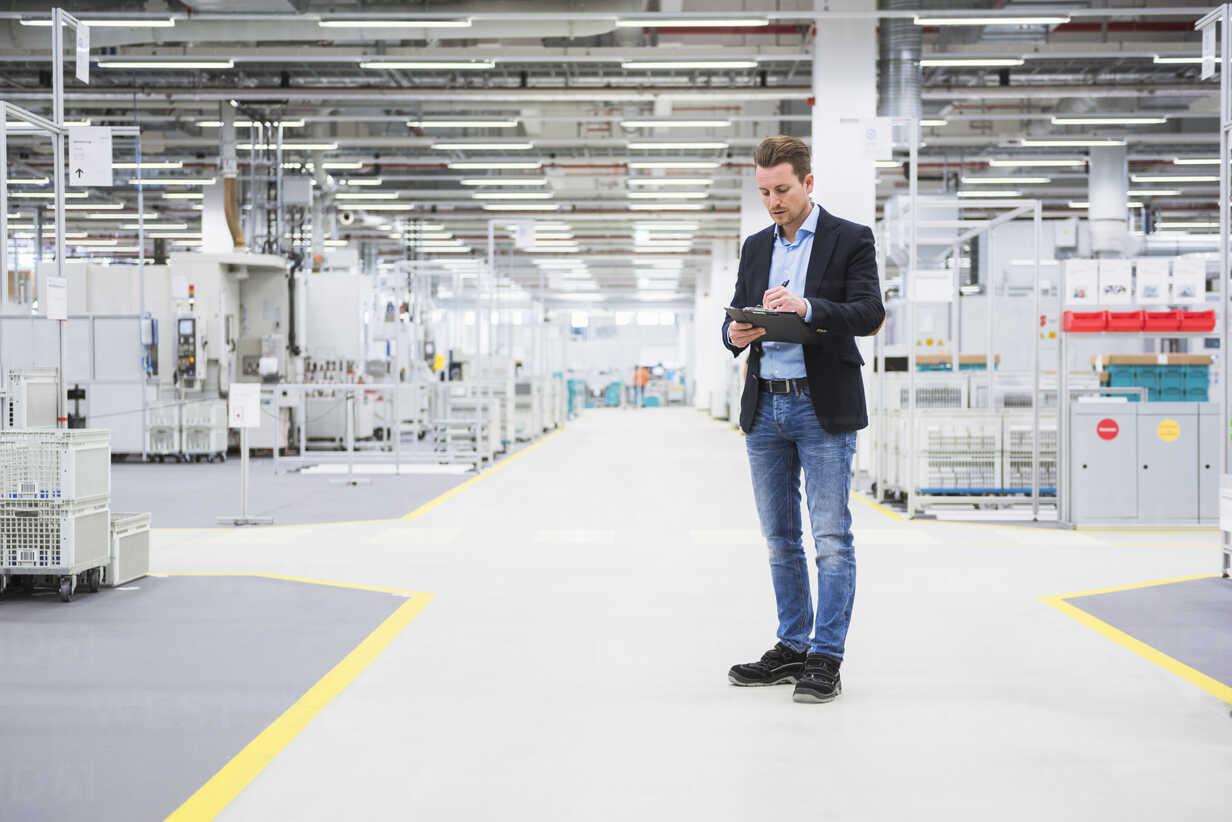 Man standing in factory shop floor taking notes - DIGF02384 - Daniel Ingold/Westend61