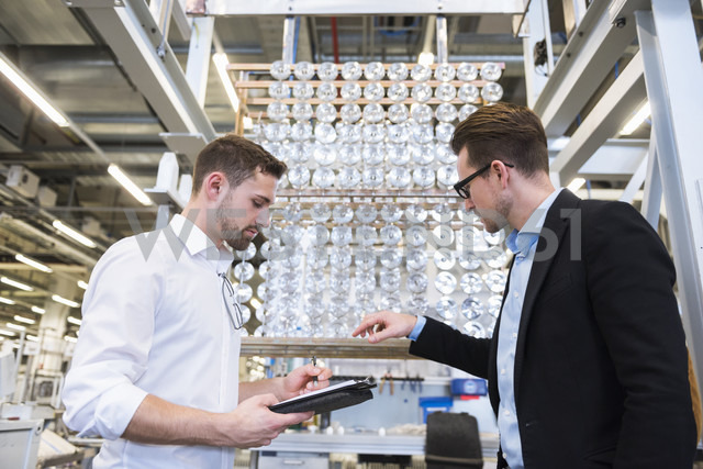Two men in factory shop floor examining products - DIGF02387 - Daniel Ingold/Westend61