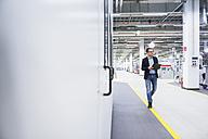 Man walking in factory shop floor taking notes - DIGF02390