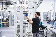 Man working in factory shop floor hanging products on rack - DIGF02393