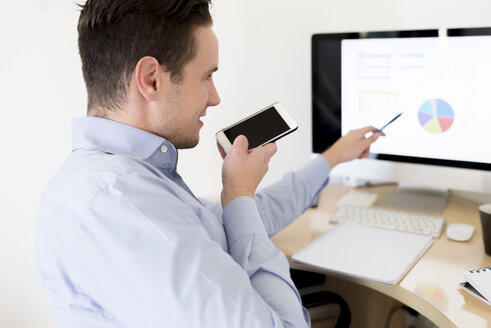 Businessman with smartphone analysing pie chart on computer screen - FMOF00242