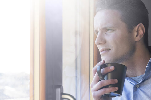 Businessman with cup of coffee looking out of window - FMOF00248