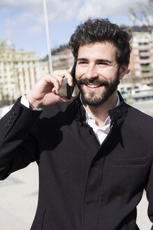 Portrait of smiling young man with full beard on the phone - ABZF01981