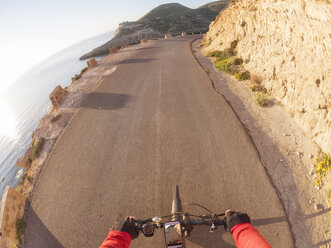 Spain, Andalusia, Cabo de Gata, personal perspective of cyclist on a street - LAF01830