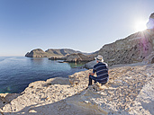 Spain, Andalusia, Cabo de Gata, back view of man looking at the sea - LAF01833