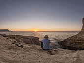 Spain, Andalusia, Cabo de Gata, back view of man looking at the sea at sunrise - LAF01836