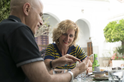 Morocco, couple sitting in a restaurant looking at cell phone - KKAF00752