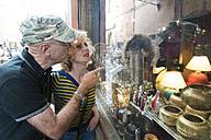 Morocco, couple looking in shop window - KKAF00755