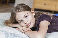 Portrait of girl lying on carpet at home - TCF05392