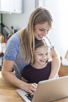 Mother and daughter using laptop in kitchen - TCF05398