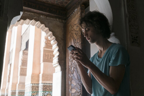 Morocco, tourist looking at cell phone - KKAF00767