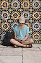 Morocco, Marrakesh, tourist sitting at tiled wall looking at cell phone - KKAF00773