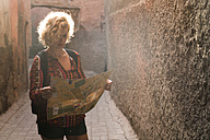 Morocco, Marrakesh, tourist standing in a passageway looking at map - KKAF00779