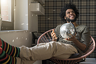 Man sitting in living room in armchair holding mirror ball - SBOF00382
