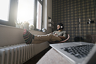 Man sitting in living room in armchair listening to music - SBOF00385