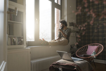 Man sitting on window sill in living room looking outside holding a cup - SBOF00388