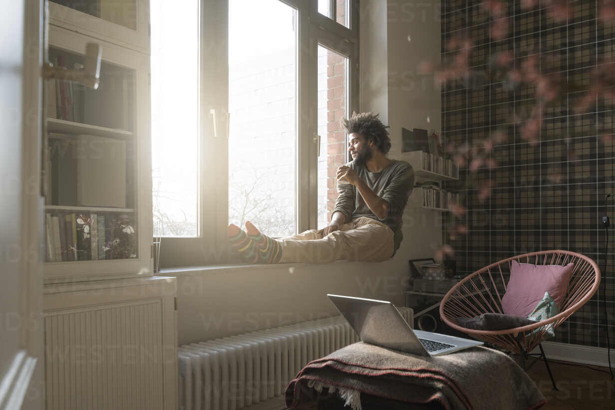 Man sitting on window sill in living room looking outside holding a cup - SBOF00388 - Steve Brookland/Westend61